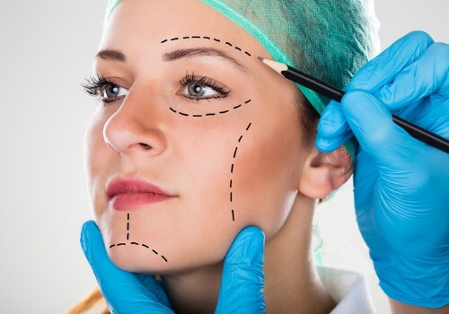 surgeon-drawing-perforation-lines-on-womans-face-picture-id842219874